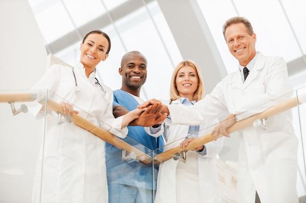 Team von medizinischen experten. niedrigwinkelansicht von vier glücklichen ärzten, die nahe beieinander stehen und ihre hände zusammenhalten, während sie sich am handlauf lehnen