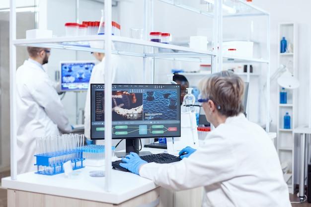 Team von mehreren ethnischen chemikern, die mit schutzbrillen zusammenarbeiten. leitender wissenschaftler im pharmazeutischen labor, der genetische forschung mit laborkittel mit team im hintergrund durchführt.