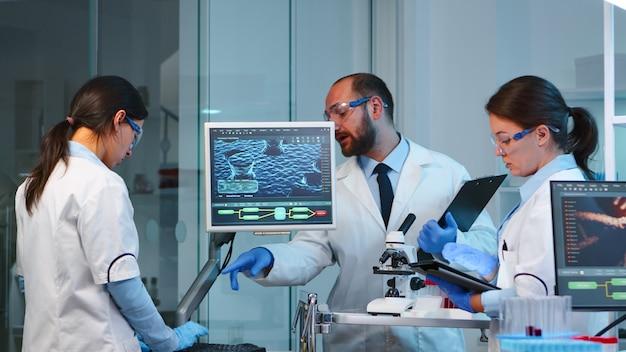 Team von mikrobiologiewissenschaftlern, die spät in der nacht über die virusentwicklung diskutieren. modern ausgestattetes labor mit pc und tablet, das notizen macht, um impfstoffantibiotika gegen covid-19 zu entwickeln.