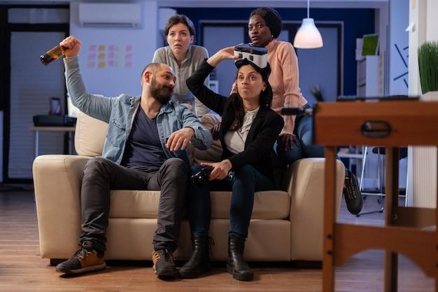 Team von multiethnischen mitarbeitern mit vr-brille nach der arbeit für party im büro. eine gruppe verschiedener menschen genießt das spielen auf der konsole mit dem controller-joystick und hat spaß beim feiern