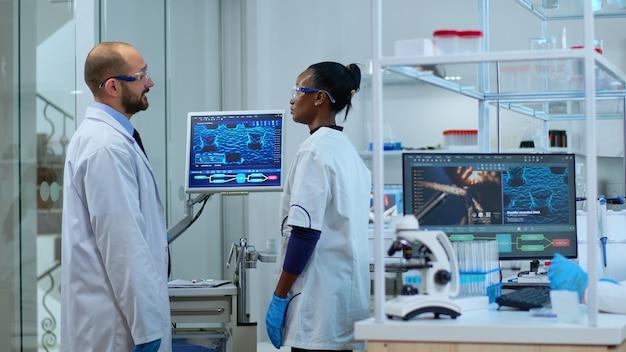 Team von multiethnischen wissenschaftlern, die im labor arbeiten und einen testimpfstoff analysieren, der arzneimitteldaten im pc überprüft. diverse gruppe von wissenschaftlern, die die virusentwicklung mit hightech für die forschung untersuchen