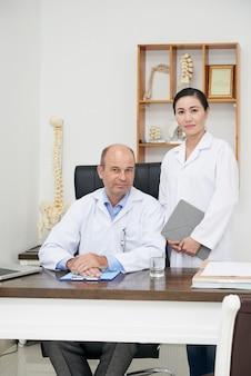 Team von osteopathen, die für ein bild im krankenhausbüro aufwerfen