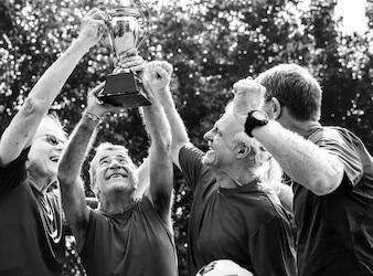 Team von reifen Fußballspielern, die den Cup gewinnen