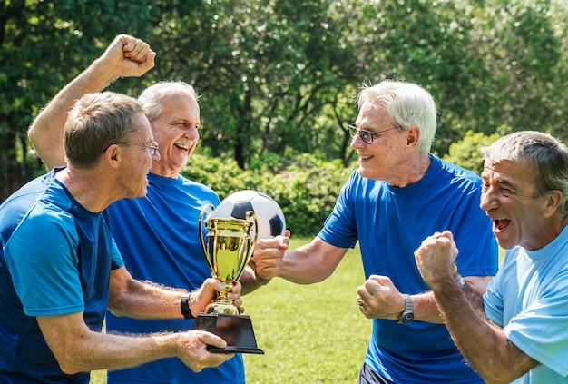Team von reifen fußballspielern, die den pokal gewinnen