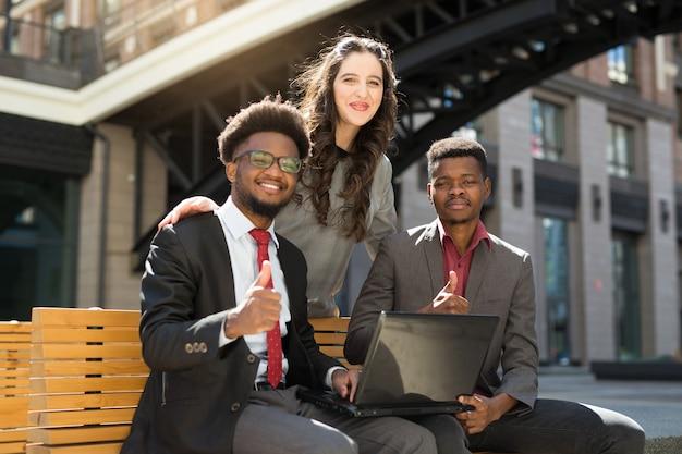 Team von schönen afrikanischen leuten auf bank mit laptop im sommer mit handgeste