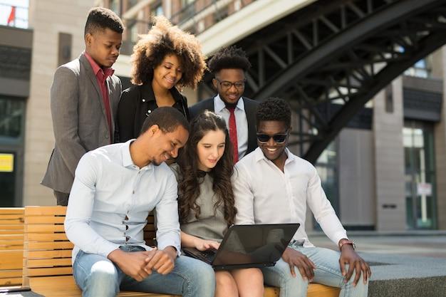 Team von schönen afrikanischen menschen auf bank mit laptop im sommer