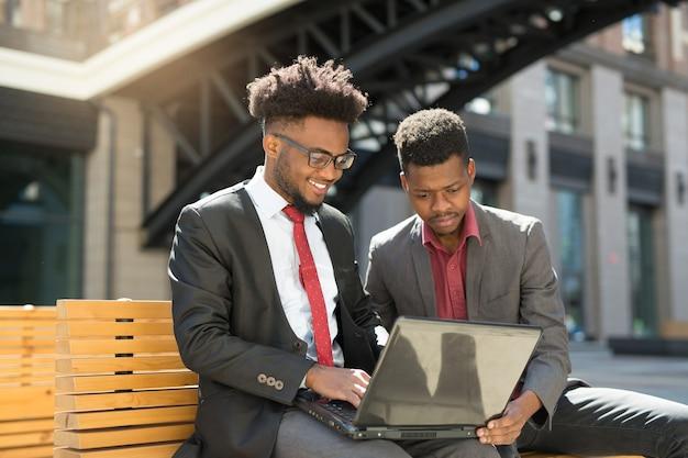 Team von schönen afrikanischen menschen auf bank mit laptop