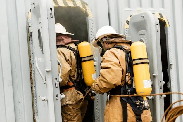 Team von seefeuerwehrleuten auf einem training, wie man feuer in einer gefährlichen mission stoppt