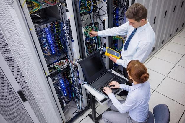 Team von technikern, die digitalen kabelanalysator auf servern verwenden