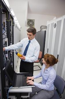 Team von technikern, die einen digitalen kabelanalysator auf servern verwenden