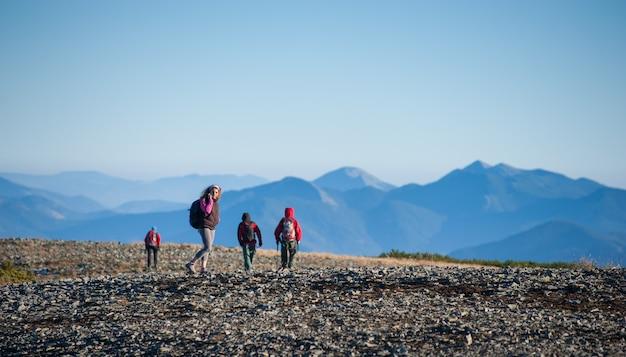 Team von vier touristen, die auf den felsigen berg plato gehen