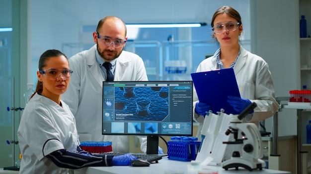Team von wissenschaftlern, die im labor sitzen und die kamera in einem modern ausgestatteten labor betrachten. gruppe von ärzten, die die virusentwicklung mit hightech für wissenschaftliche forschung und impfstoffentwicklung untersuchen.
