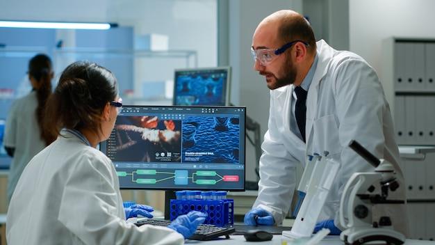 Team von wissenschaftlern, die sich sorgen um die virusentwicklung machen und in einem ausgestatteten labor diskutieren, das auf den computer zeigt. zeug zur untersuchung der impfstoffentwicklung mit high-tech-forschung zur behandlung des covid19-virus