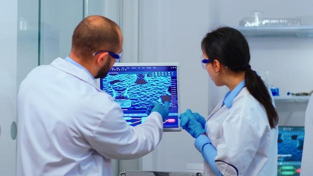 Team von wissenschaftlern, die sich sorgen um die virusentwicklung machen und in einem modern ausgestatteten labor diskutieren. multiethnisches material, das die impfstoffentwicklung mit hightech-forschungsbehandlungen gegen das covid19-virus untersucht