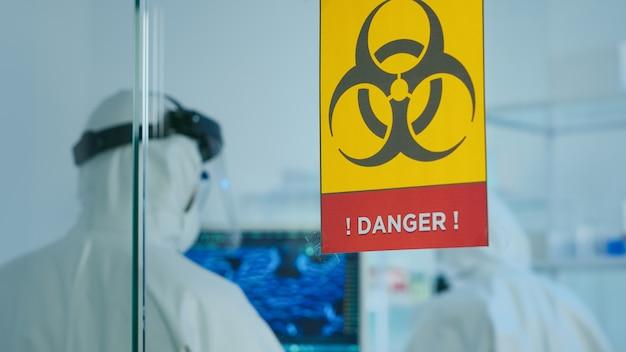 Team von wissenschaftlern im overall, die virusmutationen erforschen, die in der gefahrenzone im chemielabor arbeiten. gruppe von ärzten, die die entwicklung von impfstoffen mit high-tech zur diagnose von covid19 untersuchen