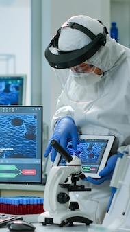 Team von wissenschaftlern in coveall, die über die virusentwicklung vor pc und tablet in einem ausgestatteten labor diskutieren. medizinisches material, das die entwicklung von impfstoffen analysiert und high-tech für die erforschung von behandlungen verwendet