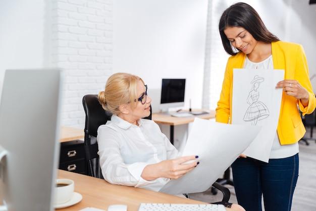 Team von zwei ernsthaften architektinnen, die im büro über skizzen diskutieren