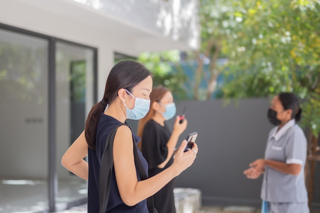 Teamarbeit der geschäftsfrau in der medizinischen maske, die am handy arbeitet.