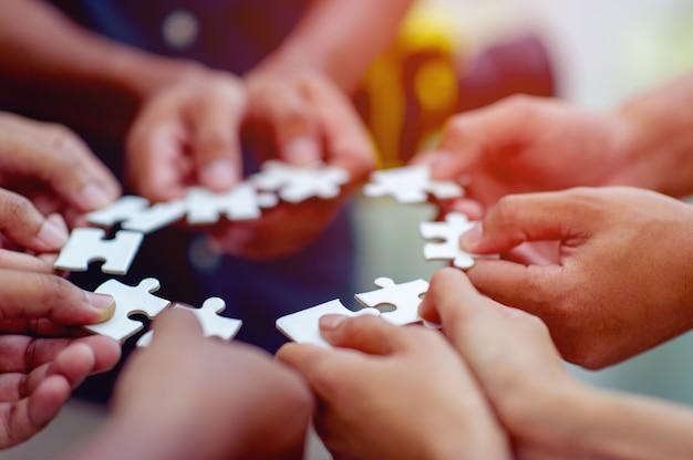 Teamarbeit, hände und stichsäge mit kraft vereinen ist ein gutes team von erfolgreichen menschen teamarbeitskonzept