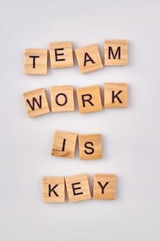 Teamarbeit ist der schlüssel. holzklötze mit teamwork und produktivitätskonzept. holzwürfel mit buchstaben auf weißem hintergrund.