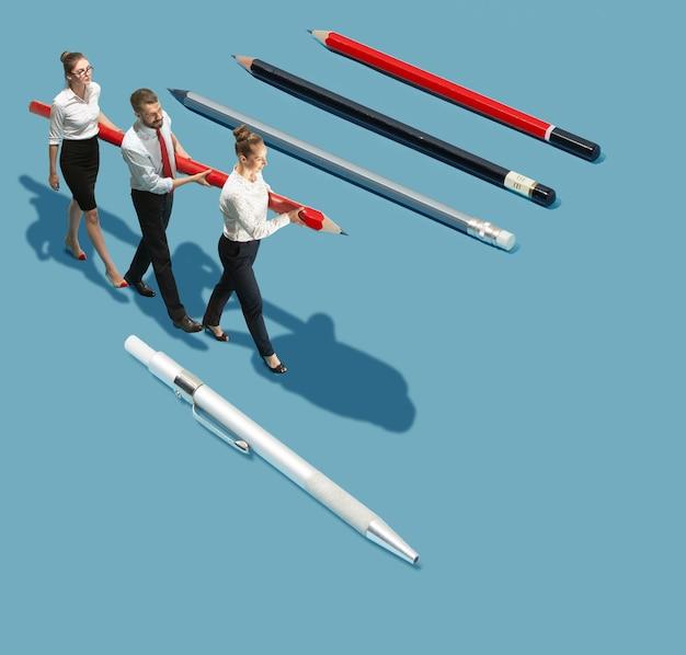 Teamarbeit, teambuilding. hohe betrachtungswinkel des kreativen modernen büros auf blauem hintergrund - große dinge und kleine arbeiter. büroarbeit, tägliche aufgabe, typische probleme und lifestyle-konzept. collage.