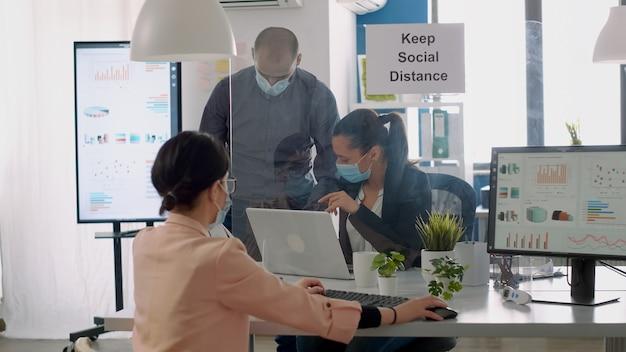 Teamarbeiter mit schutzmasken, die während der sperrung des coronavirus im geschäftsbüro am computer arbeiten. mitarbeiter halten soziale distanzierung ein, um eine ansteckung mit viruserkrankungen zu vermeiden