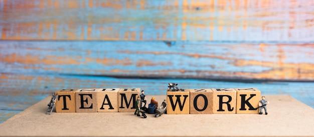 Teamarbeitswort geschrieben auf holzblock und kleinen puppen auf holzbrett