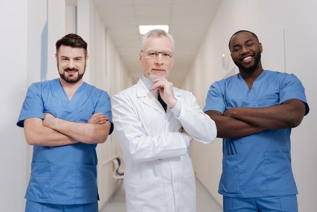 Teambuilding üben. erfreute charismatische, kluge kinderärzte, die im krankenhaus arbeiten und die zusammenarbeit genießen, während sie ihr glück ausdrücken