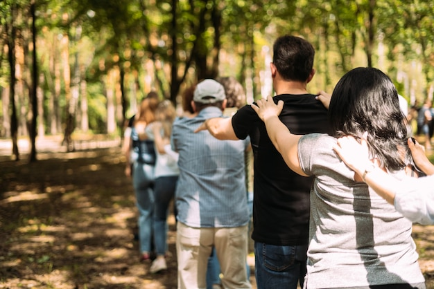 Teambuilding-übungsleute stehen hintereinander und halten ihre schultern mit den händen zurück