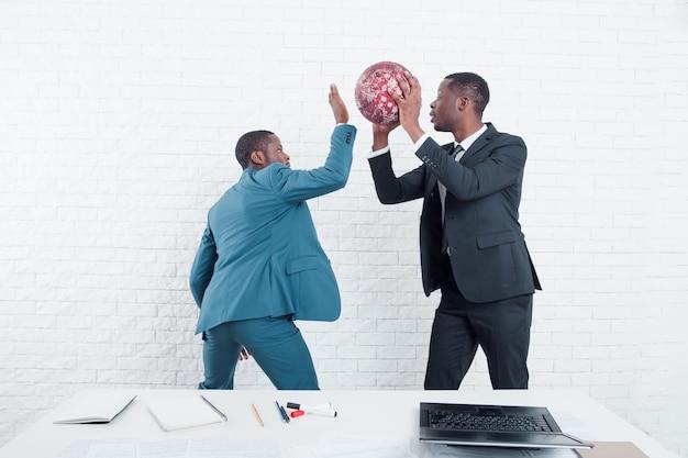 Teambuilding zur mittagszeit im büro, mit ball spielend