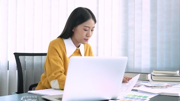 Teamdesigner, der grafik mit farbkarte auf neuem projekt mit arbeitswerkzeugen und -ausrüstung am arbeitsplatzbüro arbeitet.