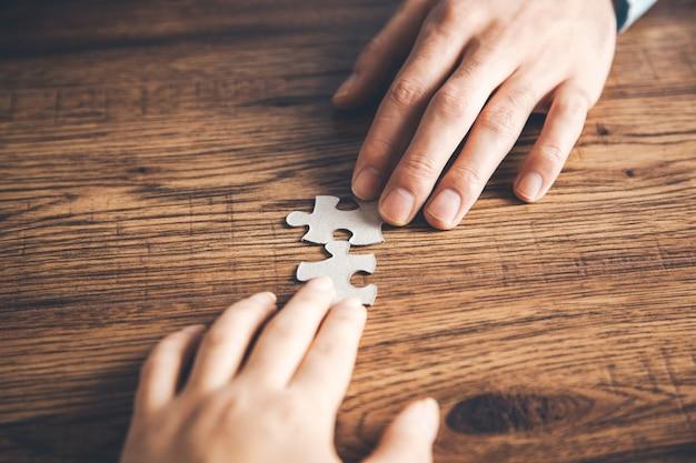 Teamhände, die puzzle auf schreibtisch halten