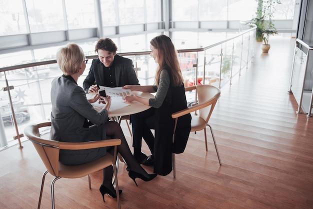 Teamjob erfolgreich. junge geschäftsführer des fotos, die mit neuem startprojekt im büro arbeiten. dokument, pläne analysieren. generisches designnotizbuch auf hölzerner tabelle, papiere, dokumente