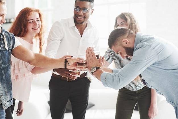 Teamkollegen trinken whisky und lachen wegen des erfolgreichen deals