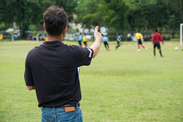 Teammanager, der seine mannschaft neben fußball oder fußballfeld trainiert