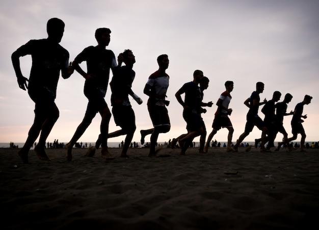 Teamtraining von jungen jungen auf dem sonnenuntergangstrand
