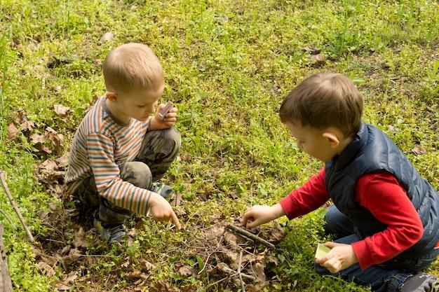 Teamwork als zwei kleine jungs ein feuer machen