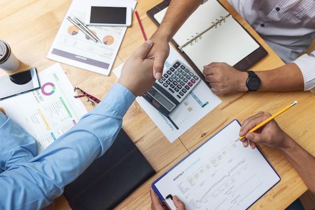 Teamwork der geschäftsmänner, die hand rütteln und geschäftsinvestitionsplan im büro besprechen