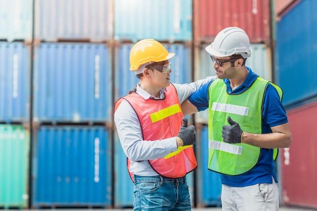 Teamwork des arbeiters, der gute daumen hoch zusammen arbeitet glückliches lächeln im containerladebereich des logistiksegments frachthafen.
