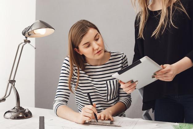 Teamwork, freiberuflich, geschäftskonzept. nahaufnahme von zwei professionellen jungen unternehmerdesignern, die an der neuen kollektion für modewoche arbeiten, durch papiere schauen, zeichnungen von kleidern machen.
