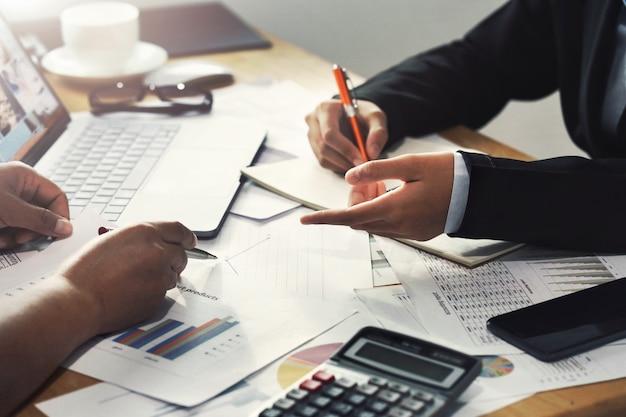 Teamwork-geschäftsfrau, die an schreibtisch im bürobuchhaltungskonzept finanziell arbeitet