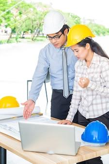 Teamwork Geschäftsmann und Ingenieur im Café im Freien mit Laptop-Computer