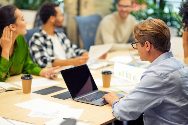Teamwork-gruppe junger gemischtrassiger menschen, die am tisch im sitzungssaal sitzen