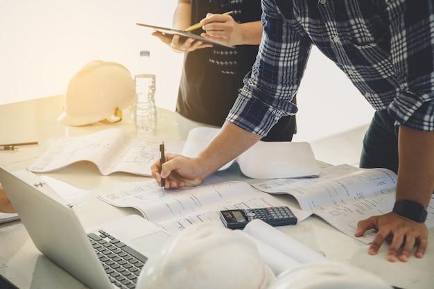 Teamwork-konzept. designer und ingenieur, die über planzeichnung am schreibtisch sich besprechen