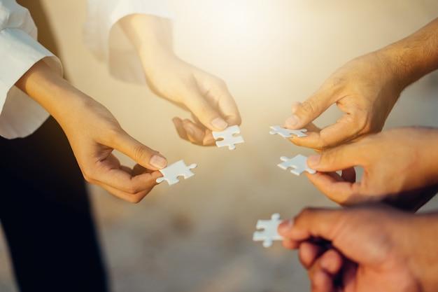 Teamwork-konzept mit den leuten, die puzzlen abschließen.
