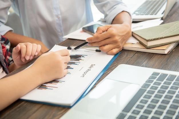 Teamwork-prozess. geschäftsleute diskutieren die diagramme und grafiken, die die ergebnisse ihrer erfolgreichen zusammenarbeit zeigen