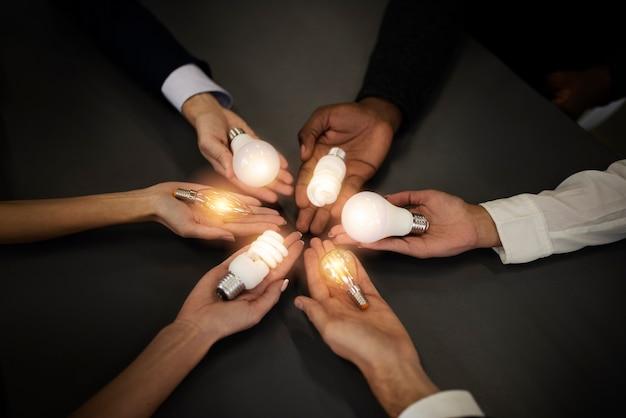 Teamwork- und brainstorming-konzept mit geschäftsleuten, die eine idee mit einem lampenkonzept des startups teilen