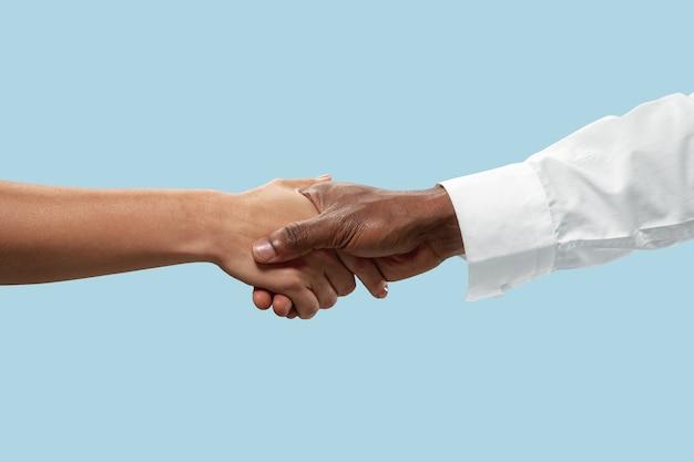 Teamwork und kommunikation. männliche und weibliche hände, die lokalisiert auf blauem hintergrund schütteln.