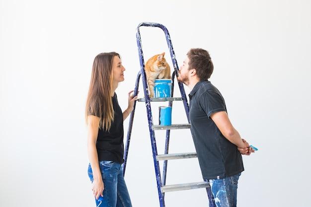Teamwork- und reparaturkonzept - junges paar mit katze, das eine renovierung in neuer wohnung durchführt.