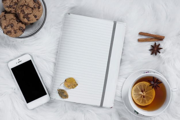 Teatime auf plaid mit geöffnetem notizbuch und smartphone